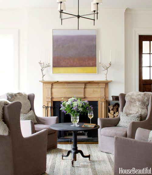 A Lakeville, Connecticut, house was given a contemporary country style by a team from Hammertown, a trio of design stores in the Northeast. Four swivel chairs from Lee Industries — slipcovered in a Covington Fabric & Design linen and topped with sheepskin pelts — offer a cozy gathering place in the family room. Antler candelabras from At Home in the Country flank a painting by Karen LeSage. Bryant chandelier by Thomas O'Brien for Visual Comfort. Pottery Barn rug.:
