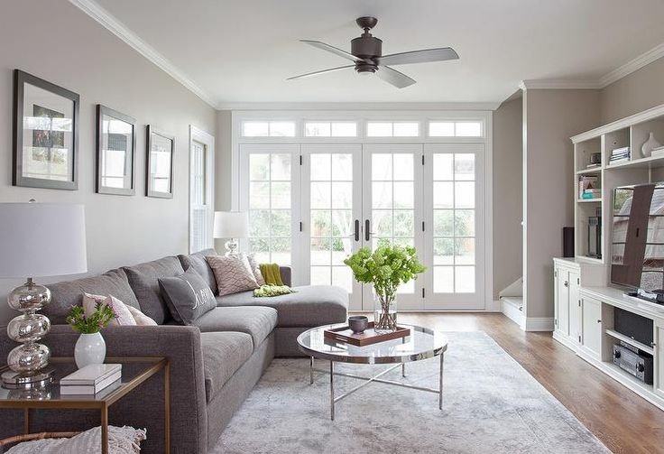 Chic living room features a gray linen sectional flanked by glass and brass end tables and mercury glass lamps facing a round glass and nickel coffee table. A gray sofa with chaise lounge faces a wall lined with a white tv cabinet fitted with shelves lined with a flat panel tv as well as cabinets.