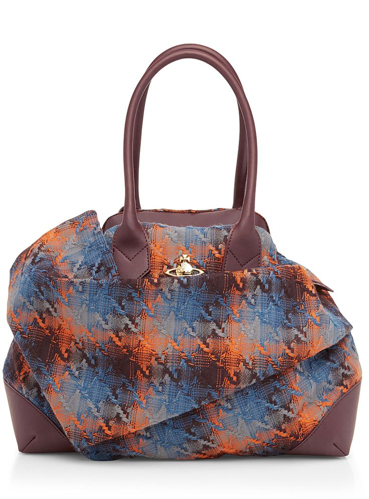 The unusual, arresting elegance of this accessory has become the calling card of Vivienne Westwood. Skilfully deconstructing both classic tartan and the practical tote-style bag, the English designer has crafted a uniquely structured piece whose cool palette boasts orange and burgundy accents. The result promises to round out your winter looks with just the right hint of warmth and British flair.    Fully lined wool-blend weave   Faux-leather accents   Metallic appliqué signature logo   Zip…