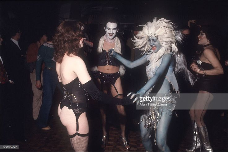 Lingerie-clad men and women dance with a woman in feathers and body paint at the opening party at the Copacabana nightclub, New York, New York, October 30, 1977. (Photo by Allan Tannenbaum/Getty Images)