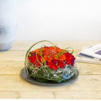 Een tropische verrassing, deze bloementaart met prachtige oranje tinten Germini's, anjer en trosrozen. De opvallende Leucospermum siert het middelpunt van het arrangement. Deze harige bol wordt ook wel Protea genoemd. Wie maak jij blij met dit tropische cadeau?