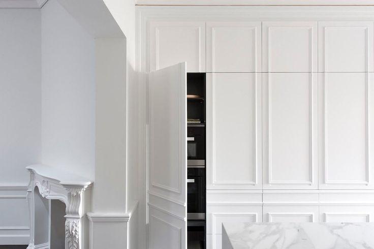 cuisine intégrée en blanc avec appareils cachés et cheminée de l'époque victorienne assortie