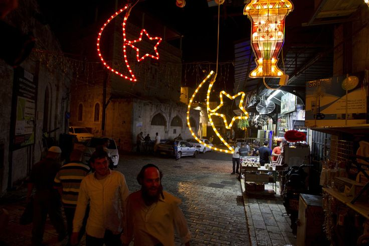 Observing Ramadan | Israeli Ultra-Orthodox Jewish men walk past Ramadan decorations, in the old city of Jerusalem on July 7, 2013, as people prepare for the upcoming Muslim holy fasting month of Ramadan. | The Atlantic/ Ahmad Gharabli/AFP/Getty Images
