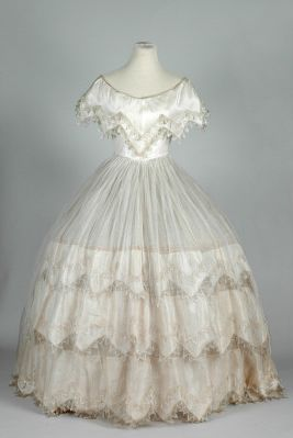 Evening dress ca. 1855-60, shimmering silk bodice with pelerine style bertha echoing a snowflake, repeated on the flounces of the sheer skirting. From the Leeds Museum  & Galleries.