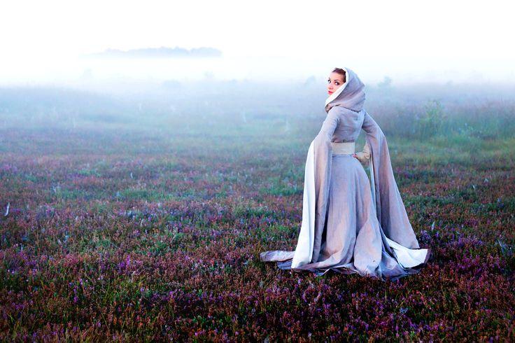 """""""Herrin der Nebel"""" Dieses Mittelalter/ Fantasy Kleid verleiht jeder Trägerin Anmut und Grazie. Das aufwendig verarbeitete Mantelkleid aus naturfarbenem Leinen ist komplett mit einem hellem, feinem Baumwolltuch gefüttert. Die Kapuze und die langen und weiten Scheinärmel lassen diesen Farbakzent durchscheinen. Dieses Kleid eignet sich wunderbar für Mittelalter- Märkte, Larp oder vlt sogar für eine märchenhafte Traum-Hochzeit?"""