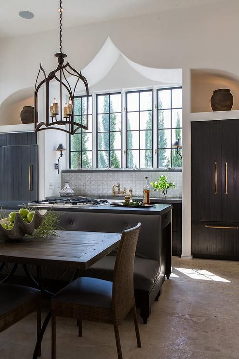 Mediterranean kitchen features a gothic lantern over black island fitted with gas cooktop lined with a black tufted dining bench paired with an iron and wood dining table surrounded by woven dining chairs.