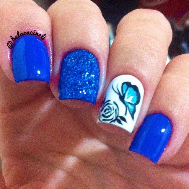 Unhas azuis, glitter azul, desenho feito a mão de borboleta e flor no anelar. Unhas decoradas. Por @belacacineli