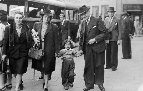 Een gezin loopt bij een bushalte. Moeder met tas en pop van haar dochtertje die ze aan de hand houdt. De vader houdt het meisje aan de andere hand vast.Plaats en jaartal onbekend.