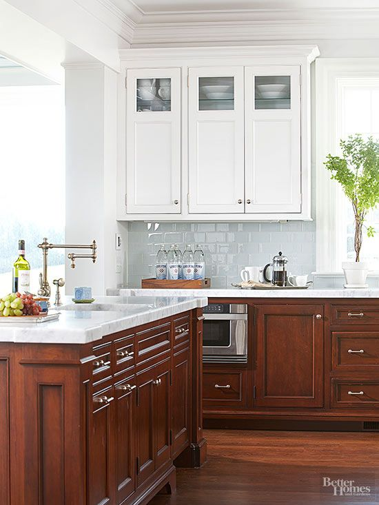 Dark walnut base cabinetry combats marks from heavy use, but upper cabinets with a white-painted finish keep this kitchen light and bright. The custom wood cabinets feature classic paneling and are grounded by stained oak floors.