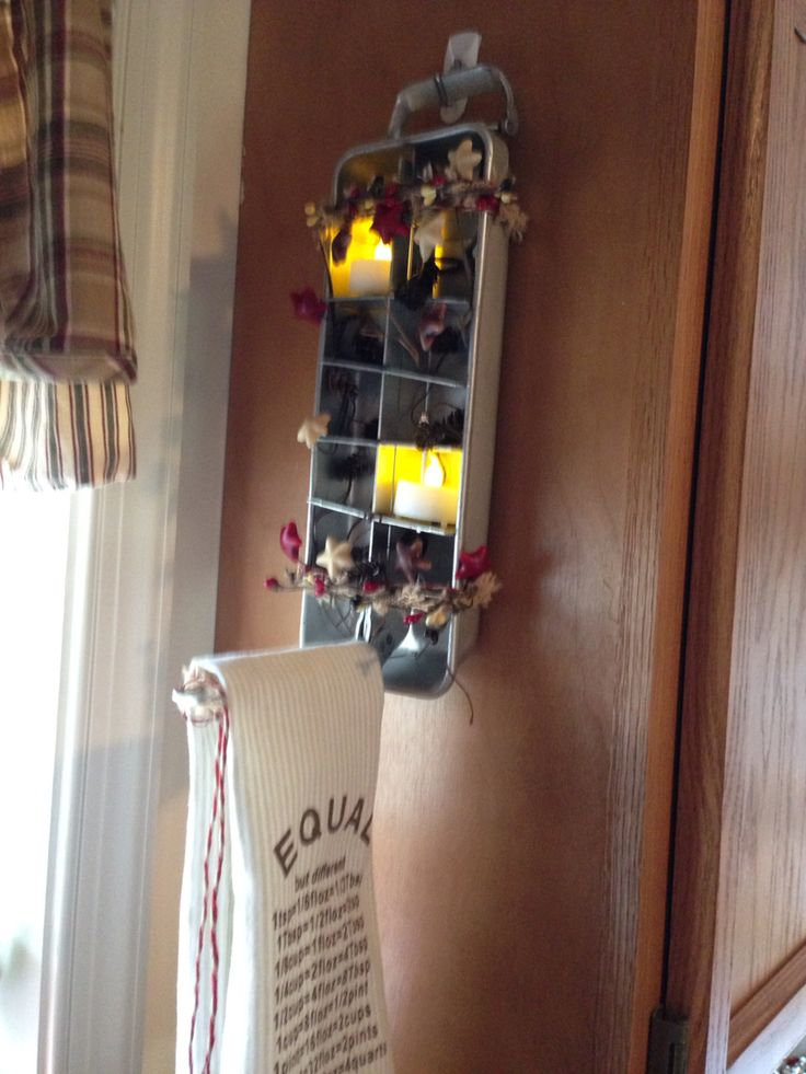 My friend made this. An old metal ice cube tray. Some battery tea lights and pretty primitive garland. I hung mine in the kitchen by my sink