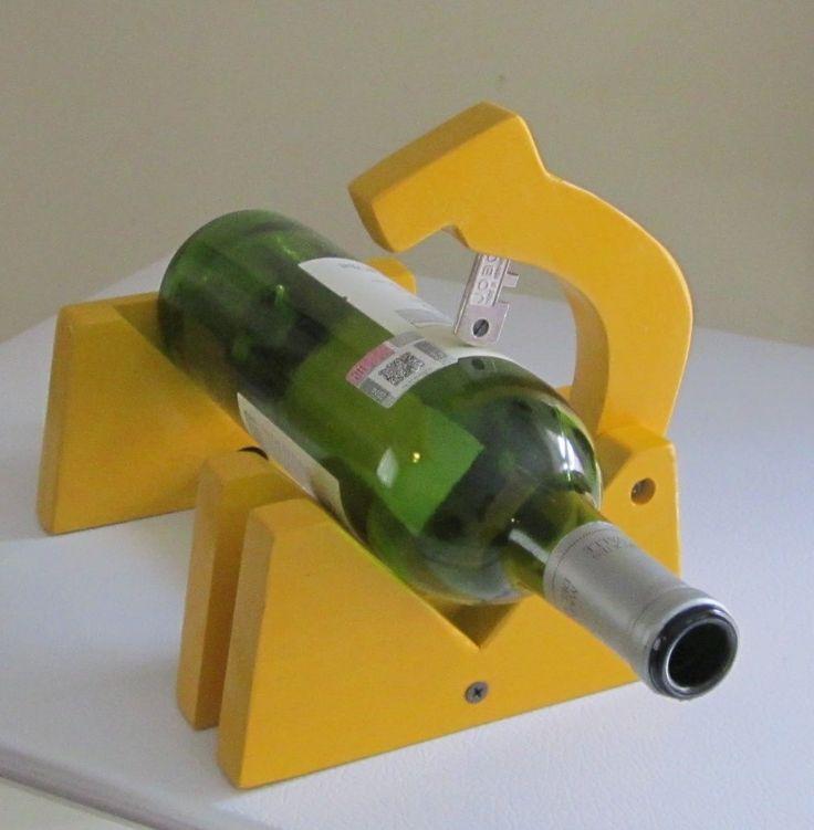 Usando un cortador de vidrio común montado en una base de madera se muestra como marcar una botellas de vidrio y con choque térmico cortarla.