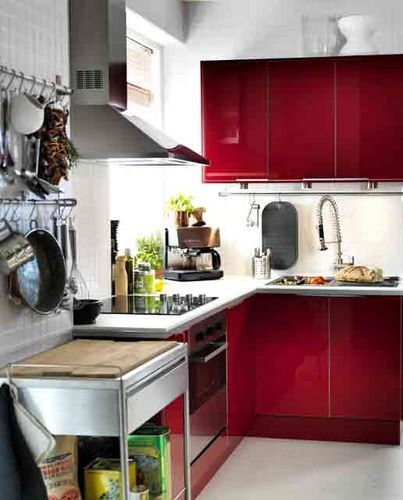 Red small kitchen. Nice but I would have used the dark, even black worktop.
