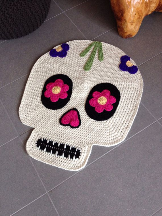 Coco the skull is our tribute to the Day of the Dead. She measures around 30 tall by 24 wide. The colors are off-white, hot pink flower eyes, royal purple flowers at the top, a dash of yellow, green and some black.