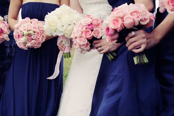 close up of bride and bridesmaids wearing dark blue dresses holding pink roses -photo by San Francisco based wedding photographer