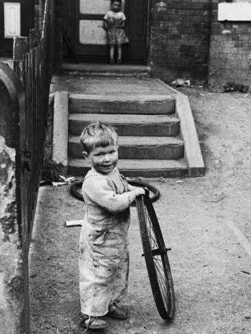 © Shirley Baker Young Toddler with Old Bicycle Wheel - Manchester, 1964