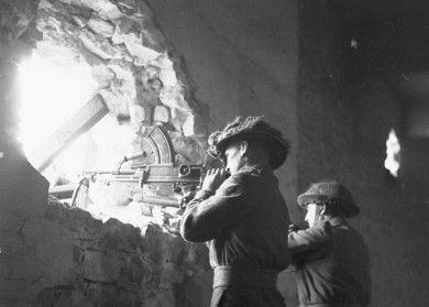 Infantrymen of The Regina Rifle Regiment manning a Bren gun position inside a captured German barracks, Vaucelles, France, 23 July 1944. Credit: Lieut. Ken Bell / Canada. Dept. of National Defence / Library and Archives Canada / PA-129131