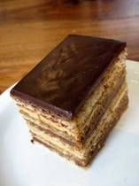OPERA CAKE Cake: 6 large egg whites, room temperature 2 T sugar 2 cups ground blanched almonds 2 1/4 cups confectioners' sugar, sifted 6 large eggs 1/2 cup flour 3 T butter, melted and cooled Espresso syrup: 1/2 cup water 1/3 cup sugar 1-1/2 T instant espresso Coffee Buttercream: 2 T instant espresso 2 T boiling water 1 cup sugar 3 T water 1 t vanilla extract 1 egg 1 egg yolk 14 T butter, at room temp