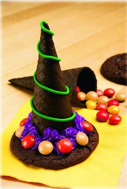 """Witch Hat Recipe: chocolate ice cream cones, chocolate chip cookies, icing, m's~ So easy, and so fun. Hold the cone and fill with m's, with icing """"glue"""" the cookie on top, then add a different color icing and more m's around the rim. Instant treat for kids Halloween party at school, girl scouts, or home"""