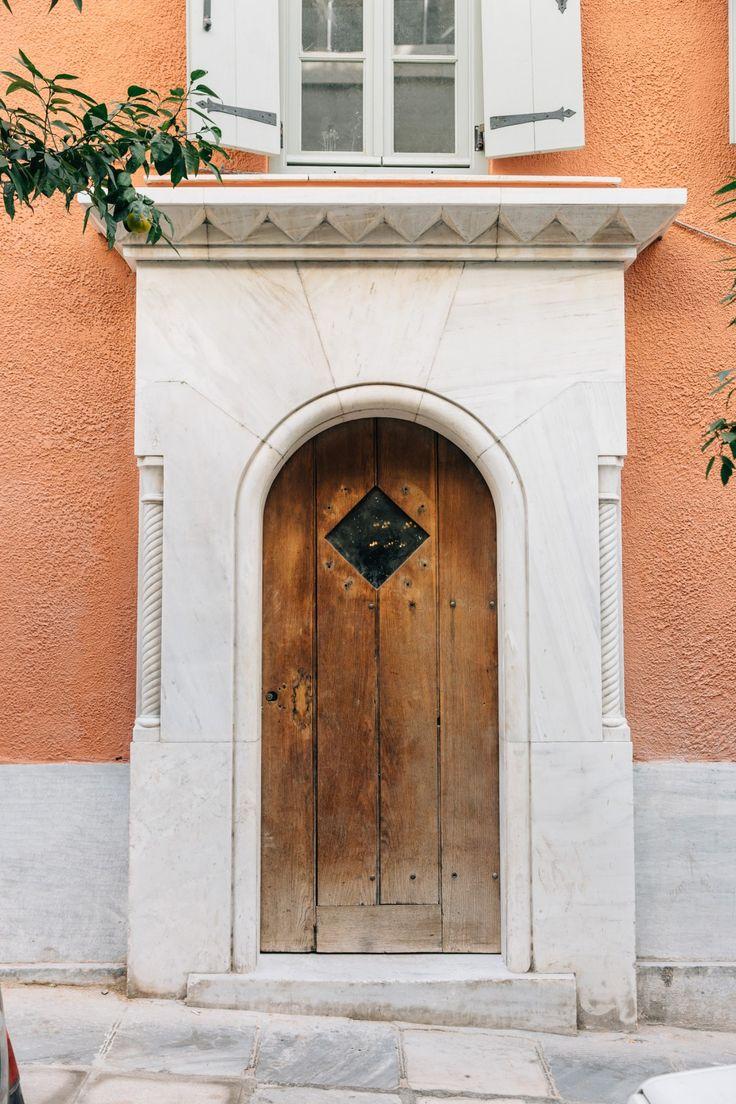 Η Ξύλινη κεντρική είσοδος της οδού Πινδάρου με το τοξωτό άνιγμα και τον γεωμετρικό μαρμάρινο διάκοσμο με ισοσκελή τρλιγωνα.