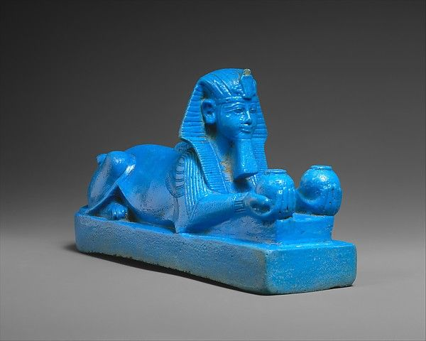 Even without the inscription, the facial features of this faience sphinx would identify it as Amenhotep III.  The graceful body of the lion transforms quite naturally into human forearms and hands. In this form, the sphinx combines the protective power of the lion with the royal function of offering to the gods