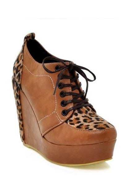 High platform wedge boots with lace up closure, featuring a rounded toe lace up closure with metal eyelets, leopard suede design to back counter, ankle length.