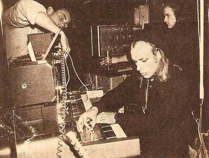 Brian Eno, On Stage Live, with band 'Harmonia' (Michael Rother [Kraftwerk, Neu!], Hans-Joachim Roedelius and Dieter Möebius [Cluster]), at 'Fabrik', Hamburg, [Germany], (1974) - image © courtesy of Rory W.
