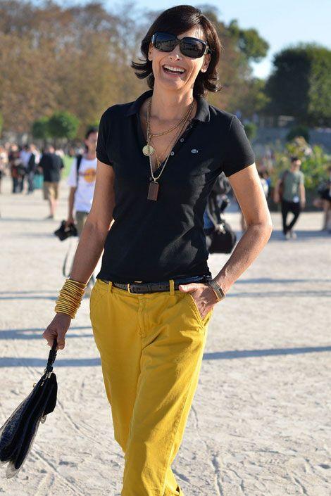 Inès de La Fressange sports a classic Lacoste polo shirt and colorful chino trousers