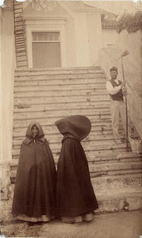 Açoreanas de capote e capeto = AÇORES (Azores) - PORTUGAL, early 20th century capote e capelo - Two women, one facing front and one sideways, in capotes (long cloaks and hoods) at the foot of a stairway. In the background is a man whitewashing. This is thought to be the Bom Despacho Chapel.  - pin de Robin.