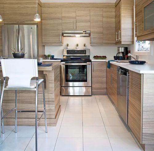 Le bois est un matériau chouchou dans les cuisines actuelles, mais il peutfaire monter le total de la facture des travaux en flèche. Ici, la mélamineimitation bois a suffi pour donner un air de jeunesse à ce décor, et ce, àpetit prix. Les comptoirs en stratifié, le plancher ainsi que les tabouretsblancs contribuent à donner une touche d'éclat à l'ensemble.