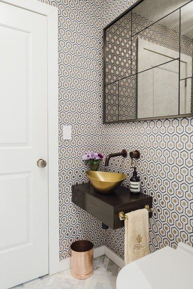 The master bath's pocket door closes off the shower and sink vanity to create a powder room for guests. The wallpaper is a David Hicks design by Cole & Son, and the mirror is from West Elm | archdigest.com