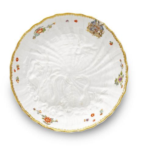 A Meissen saucer from the Swan Service, circa 1739. Modelled by J.J. Kaendler in low relief with swans swimming among bulrushes and a crane to the left with another in flight overhead, all on a shell-moulded ground, the rim painted with the arms of Brühl/Kolowrat-Krakowska, three flower sprigs and further scattered blooms, the rim with a gilt border, 13.8cm diam., crossed swords mark in underglaze-blue, faint impressed Dreher's mark (very minor wear to gilding)