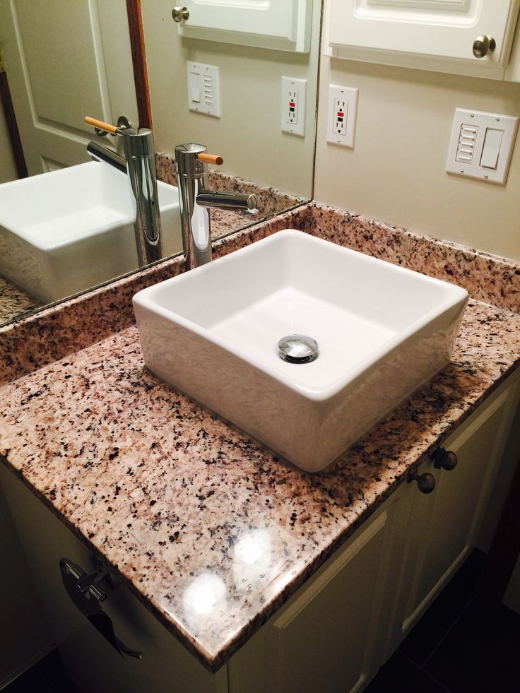 On this renovation we installed a new light, vanity top, square vessel sink and single lever faucet.