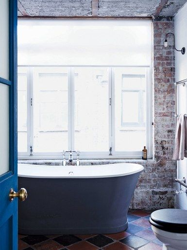 An Aston Matthews bath takes pride of place in front of this window, which required only light restoration but was updated with new bronze hardware from Frank Allart. A simple white roller blind is ideally suited to the unadorned aesthetic, and a Fritz Fryer wall lamp had its shade removed for a more industrial feel | archdigest.com