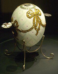 1916 Uovo dell'ordine di San Giorgio -  L'uovo è cesellato e smaltato con un pergolato di foglie verdi e piccole croci di San Giorgio e coperto da smalto perlaceo traslucido. Un nastro dell'Ordine Imperiale di San Giorgio, in smalto arancio traslucido e nero, è drappeggiato attorno all'uovo e forma dei fiocchi. Sotto due dei fiocchi, contornate dal nastro, sono poste due medaglie che, per mezzo di piccoli pulsanti, si aprono sollevandosi.