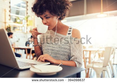 Portrait of young african woman drinking coffee and using laptop at a cafe.