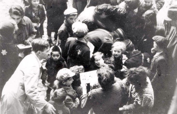 Lodz, Poland, 1941, Nachman Zonabend distributing sweets to children at Hanukkah
