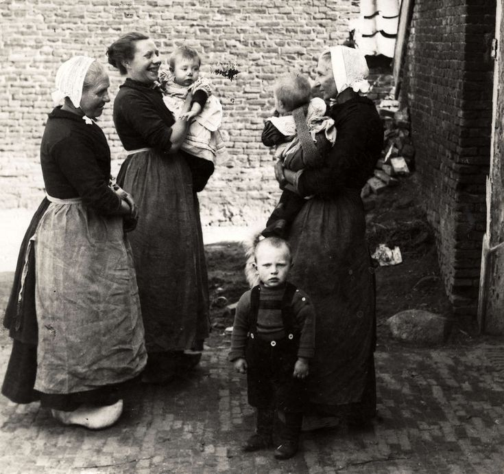 Klederdrachten. Vrouwen in klederdracht staan met kinderen op de arm en rond hen, op het erf met elkaar te praten. Rijssen, Nederland, 1925. Serie van 2 fotos.