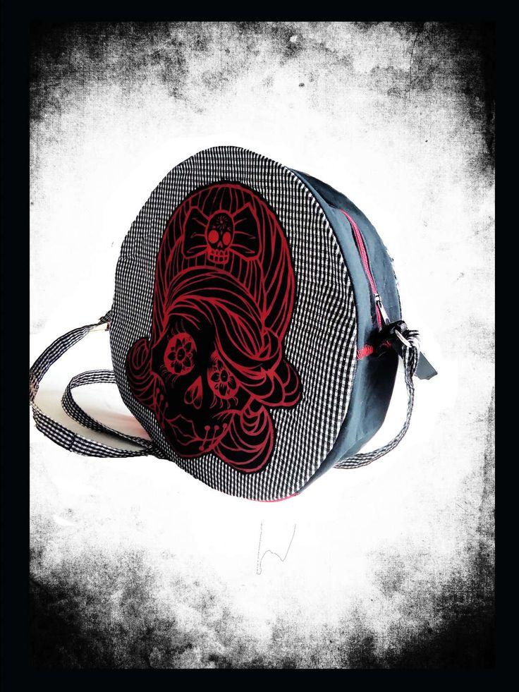 Kulatá kabelka s muertou. Extravagantní, originální kabelka z černobílé drobné kostičky, kombinace černé a červené. Popruh u kabelky je regulovatelný.