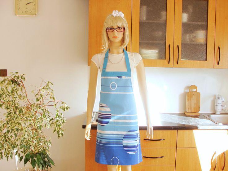 """Volná decentní kuchyňská bílá zástěra s moderním modrým dekorem.  Úvaz kolem krku v bledě modrém provedení  stavitelný systémem """" Roll On """" opatřený chromovou přezkou - možnost zkrátit. Vzadu dlouhé zdvojené šňůry na uvázání za pasem v bledě modrém provedení ."""