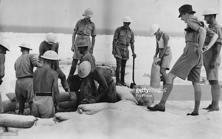 British politician Sir Anthony Eden (second right) watching a sandbagging party at work, on a visit to Palestine, November 11th 1940.