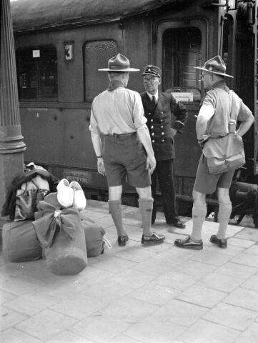 augustus 1951. Afbeelding van twee padvinders (hopmannen?) in gesprek met een hoofdconducteur van de N.S. op het perron van het N.S.-station Utrecht C.S. te Utrecht, voor aanvang van een treinreis naar de Jamboree in Oostenrijk.