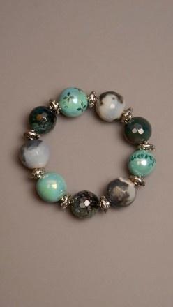 Bracciale elastico con perle in porcellana, pietre e dettagli in acciaio.