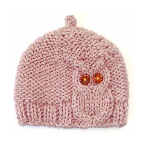 Questo berretto di lana grossa mette in mostra un cavo grassetto gufo che si siede squat nelle nervature di bordo in maglia. Non lampeggiano gli