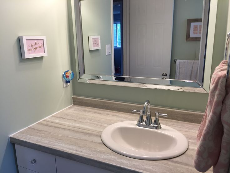 """The vanity was an odd size and we didn't want to do a custom order. These are two cabinets from Lowes and a laminate counter top also from Lowes. We reused the faucet we had previously but the sink is new (Lowes) as is the mirror (home sense), an upgrade from the builders mirror that was there before! The new vanity is also at a r hilarious height whereas the old one was significantly lower. Small picture from Winners. """"Hello gorgeous""""."""