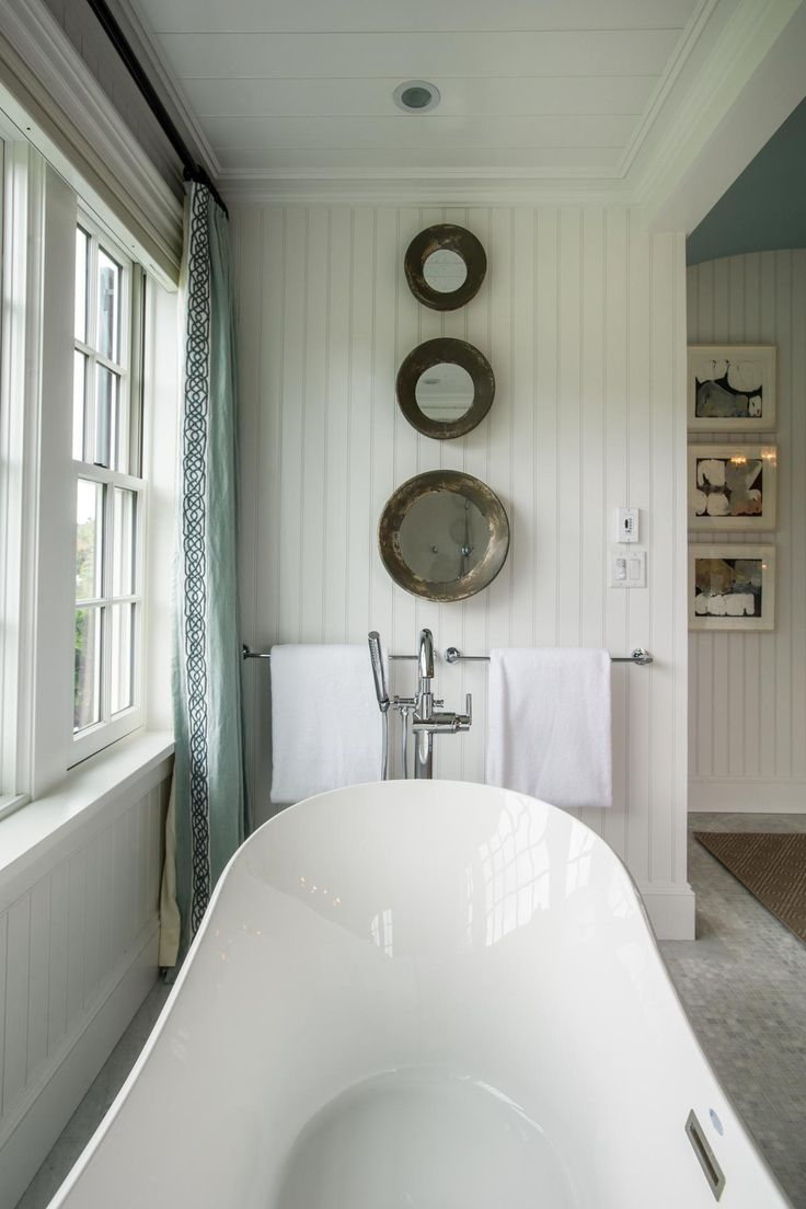 To reflect light and add depth to the room, a trio of mirrors descends from the ceiling to the towel rod. Crisp, white towels give the space a hotel-inspired look. #HGTVDreamHome great idea and love the tub