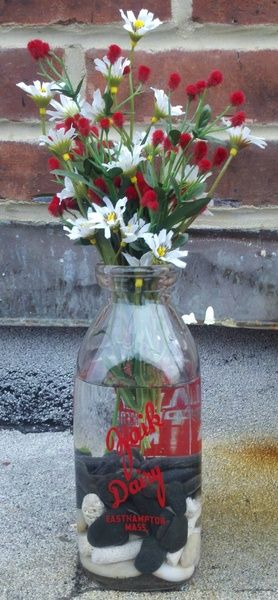 old milk bottle filled with beach stones