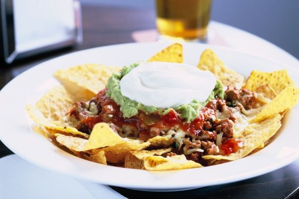 Dive into a piping hot bowl of beef nachos topped with melted cheese - yum!