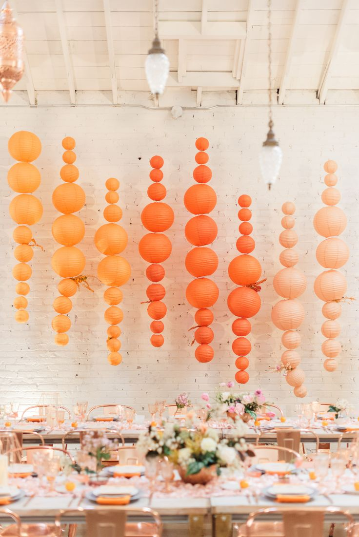 Now, if you look closely, you'll see that these are actually paper lanterns—but don't fret! You can easily DIY this design using balloons. We love the ombré-like colors and asymmetrical design as a backdrop for your photo booth or entire reception.