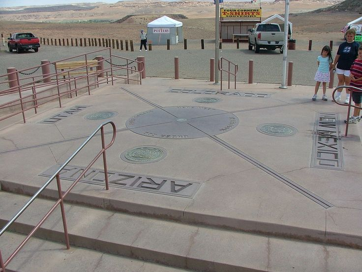 """A concrete pad with the state seals of the four states. In the center of the pad is a red disk reading """"Four States here meet, in freedom, under God."""" Inside that disk is a smaller bronze disk."""