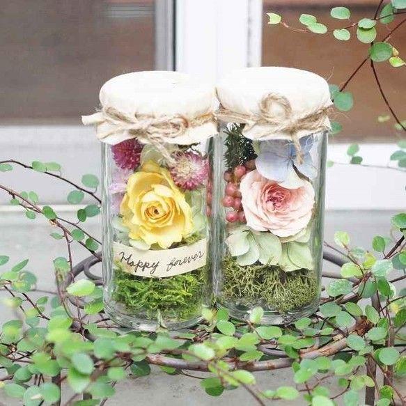枯れないお花でアンティークなボトルにアレンジしました。 通常はボトルフラワーに入れていますお花です。 お花はボトルフラワーを作るドライ加工で制作してありますので生花に近い綺麗なお色、形です。 瓶の中にはシリカゲルが入っていますので5年以上美しいままです。皆様のお幸せを祈ってアンティークな紙に『happy forever~永遠にお幸せに、ずっと幸せに』と書きました。 フタは接着剤で開きませんのでご了承下さい。 金額もボトルフラワーのお試しとしてお安く出品しました。使用材料・・【A】ファンシーローラ(ピンクバラ)、秋色アジサイ、ペッパーベリー、モス。 【B】フレアー(イエローバラ)、センニチコウ、スターチス、秋色アジサイ、モス。 サイズ W5㎝、H11㎝。【A】の中に入っていますアジサイは自然に変色して同じアジサイながらグリーンとブルー2色に変わりました。 自然のお色って綺麗ですね。ファンシーローラは中央の色が濃くて周辺が薄くなるかわいいバラです。 【B】のフレアー小さいながら綺麗なフォルムです。 ボトルフラワーと違ってカジュアルに仕上げました。_ _ _ _ _ _...